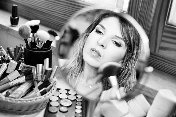 una donna si trucca guardandosi in uno specchio tondo