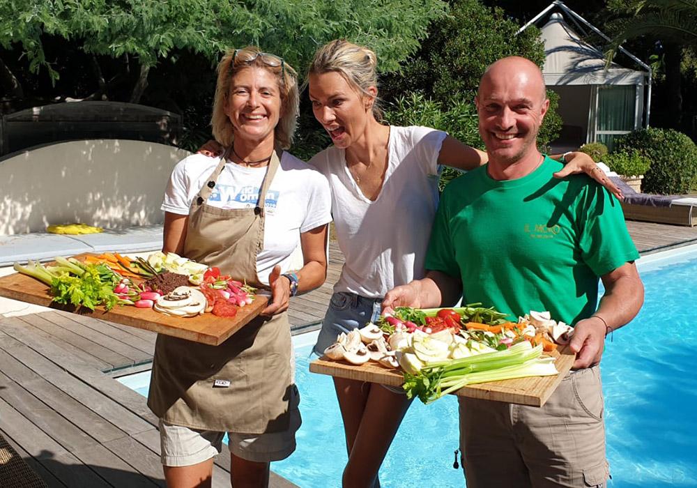 due donne e un uomo sorridono mostrando ingrendienti freschi e verdure pronte per essere cucinate