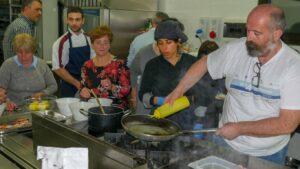Cuoco e partecipanti preparano dei piatti in cucina