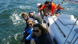 persone sedute vicino al fianco di una barca a vela