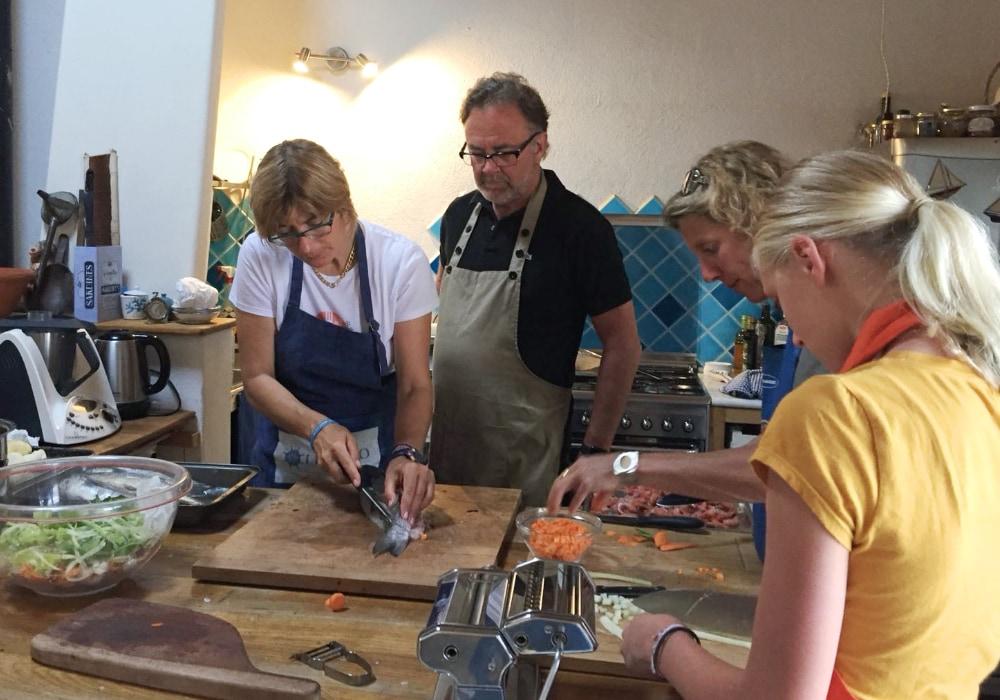 tre donne ed un uomo preparano da mangiare in cucina. Sul tavolo pesce, verdure ed attrezzi da cucina