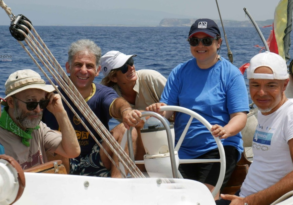 un gruppo di persone in barca a vela, con il mare sullo sfondo ed una ragazza al timone della barca