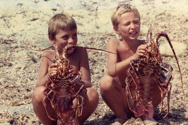 bambini in posa con due aragoste giganti